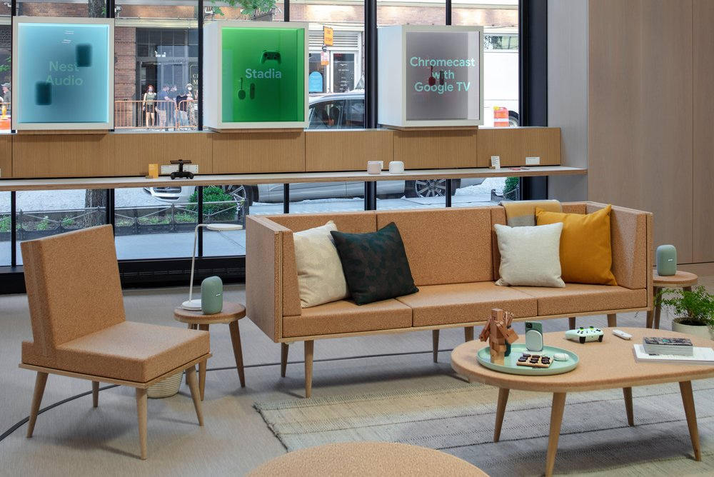 A couch, chair and coffee table stand in front of the Discovery Boxes inside Google's retail store.